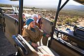 Happy senior woman getting into safari off-road vehicle