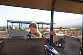 Happy mature woman getting into safari off-road vehicle