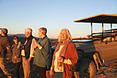 Carefree woman on safari drinking champagne at sunset