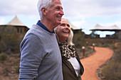 Happy senior couple on footpath outside safari lodge