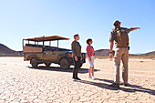 Guide talking tourists in sunny arid desert South Africa