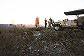 Group drinking tea outside off-road vehicle at sunrise