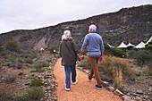 Senior couple holding hands on footpath