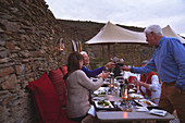 Senior friends toasting wine glasses on restaurant patio