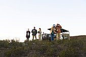 Group drinking tea and using binoculars on hill