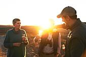 Safari tour guide pouring champagne for senior couple