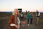 Portrait happy senior woman drinking champagne on safari