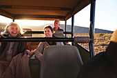 Happy friends riding in safari off-road vehicle