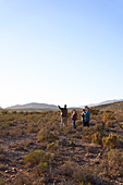 Guide talking with group in sunny remote grassland