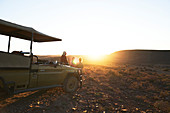 Group watching sunset by off-road vehicle South Africa