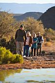 Safari tour guide leading group on sunny wildlife reserve