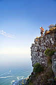 Couple on cliff over sunny ocean Cape Town South Africa