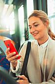 Woman using smart phone on bus