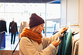 Woman shopping in clothing store, checking price tag