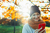 Woman with smart phone in autumn park