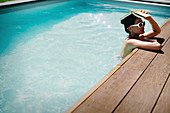 Woman holding book overhead in summer swimming pool