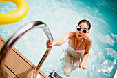 Woman at swimming pool ladder