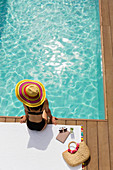 Woman in sun hat and bikini relaxing at poolside