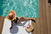Woman in sun hat sunbathing, relaxing at summer poolside