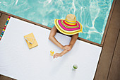 Woman in sun hat applying sunscreen in swimming pool