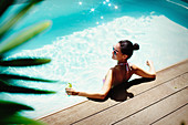 Woman relaxing with cocktail in summer swimming pool