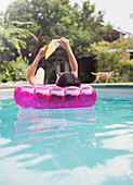 Woman relaxing, reading book on inflatable raft