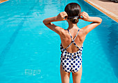 Girl in polka-dot bathing suit at summer poolside