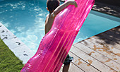 Boy with pink inflatable raft at summer poolside