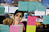 Businesswoman with adhesive notes planning in office