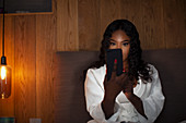 Woman using smart phone in dark bedroom