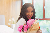 Portrait woman with bouquet of pink peony flowers