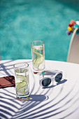 Cucumber water and sunglasses on poolside patio table