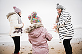 Family in warm clothing on winter ocean beach