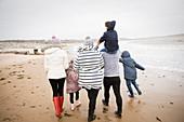 Family in warm clothing walking on winter ocean beach