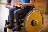 Boy in wheelchair using digital tablet