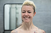 Carefree woman with tattoos laughing in bathroom