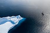 Ship sailing past arctic iceberg on