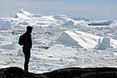 Silhouette man looking at glacial ice melt Greenland