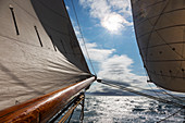 Sail and wooden sailboat mast over tranquil Atlantic Ocean