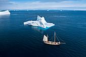 Ship sailing past iceberg on blue Atlantic Ocean Greenland