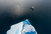Drone point of view ship sailing past iceberg on ocean