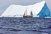 Ship sailing past majestic iceberg on