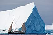 Ship sailing below majestic iceberg