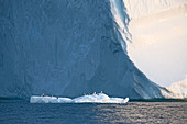 Birds perched on melting ice below iceberg