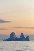 Majestic iceberg formation over sunset