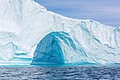 Majestic iceberg arch over blue ocean Greenland