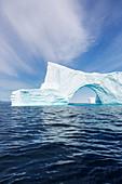 Majestic iceberg arch over blue Atlantic Ocean Greenland