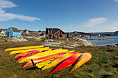 Vibrant coloured kayaks in grass Disko Bay West Greenland