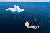 Ship sailing past majestic iceberg on blue