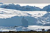 People hiking along melting glacier Greenland